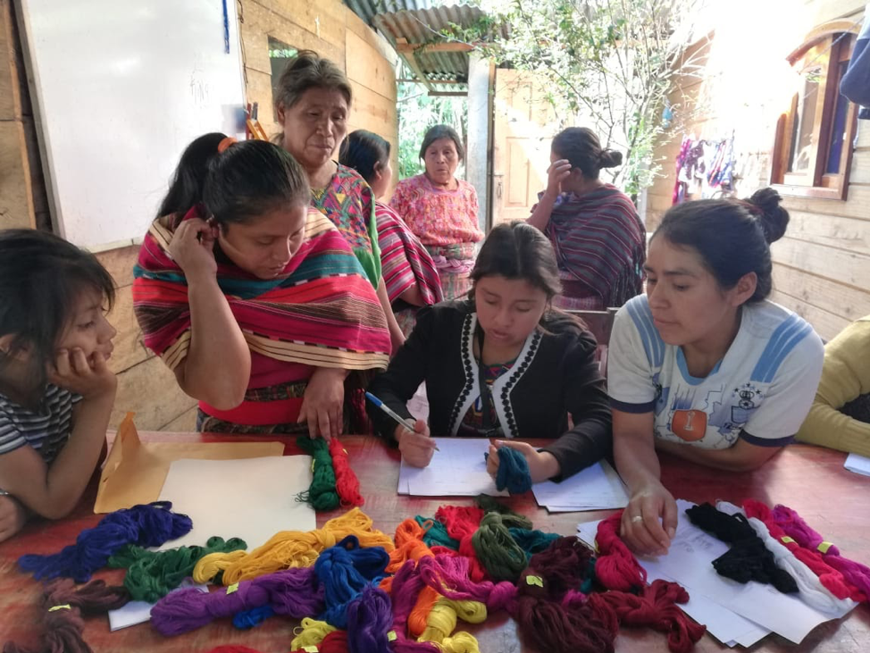 A young Ixil girl writes in a notebook on a table surrounded by fabric. Other women and girls hover around her to assist.